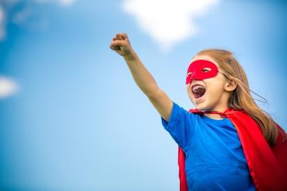 Funny little girl plaing power super hero.